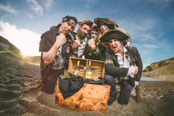 left to right it's: - The Admiral (bass) - Johnny 'Danger' Danger (guitar) - Ashtiki The Caveman (drums) - Scarlett Van Dyke (ukulele) - The Captain (vocals)